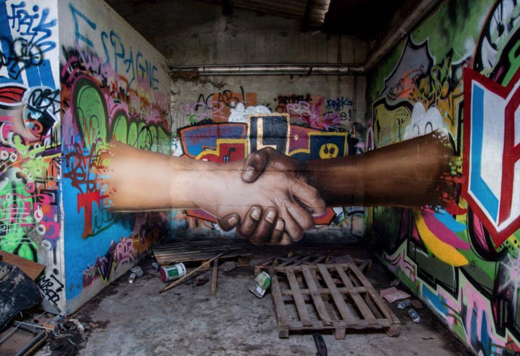 A mural of a black hand and white hand holding hands
